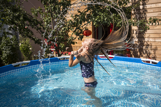 Girl in the garden pool splashing with water