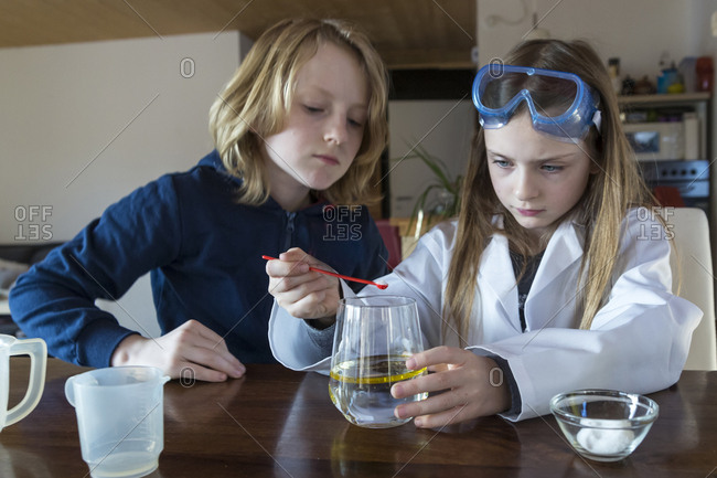Two children using chemistry set at home