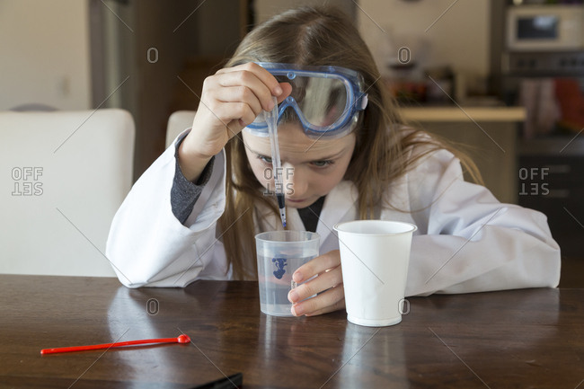 Girl wearing work coat and safety glasses using chemistry set at home