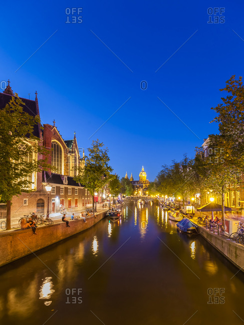 Netherlands, Amsterdam - August 23, 2016: De Wallen- Oudezijds Voorburgwal- Oude Kerk and town canal and evening twilight