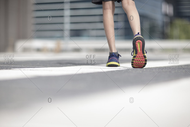 Legs of boy in sports shoes walking in the city