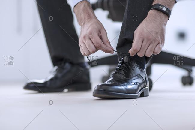 Man tying his black formal shoes