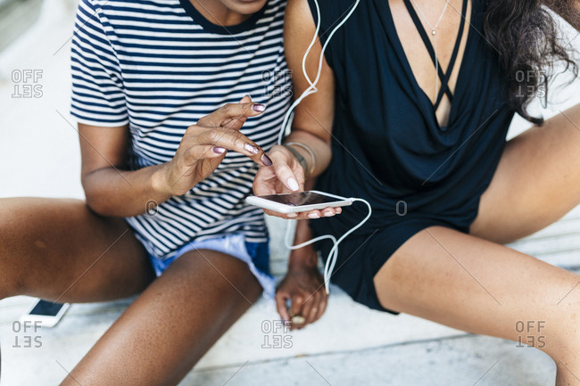 Two friends sitting on stairs listening music together with earphones and smartphone- partial view