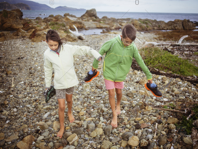 Mixed race brother and sister carrying their shoes on rocky beach