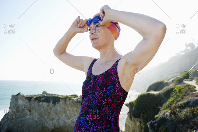 Older Caucasian woman putting on goggles on beach