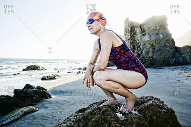 Older Caucasian woman crouching on rock on beach