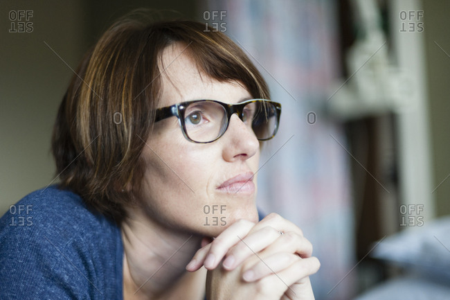 Caucasian woman thinking with hands clasped