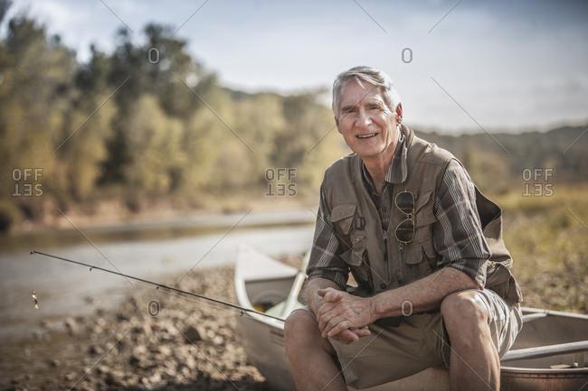 Older Caucasian man holding fishing rod near river