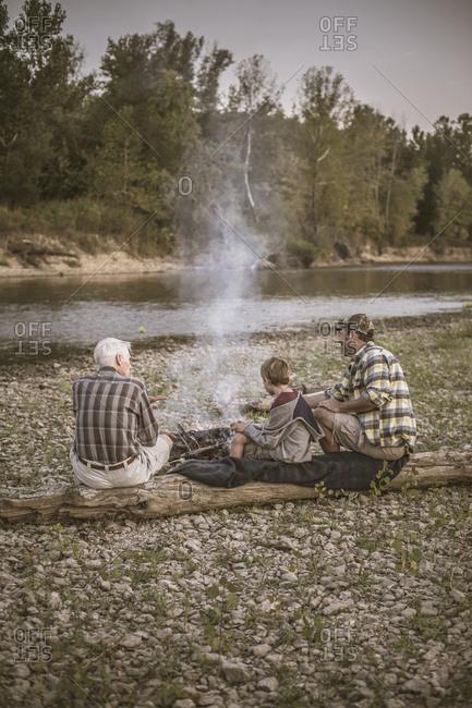 Three generations of Caucasian men relaxing near campfire