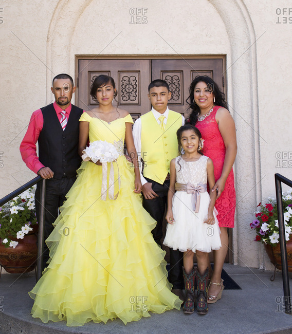 Hispanic family celebrating quinceanera outside Catholic church