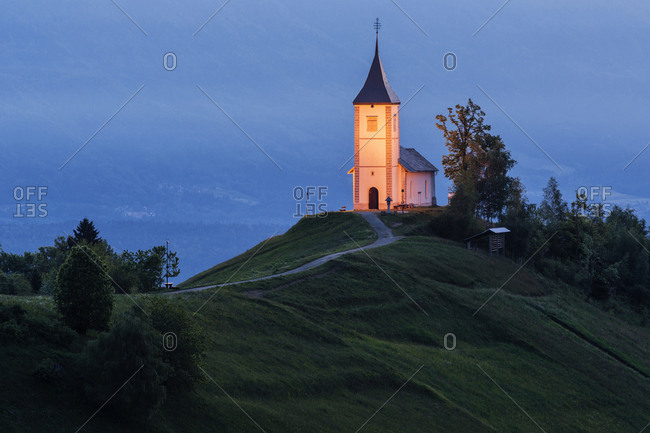Illuminated church tower on remote hilltop