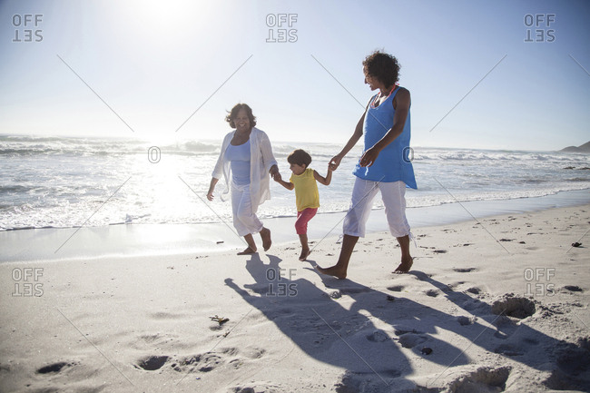 Mixed race grandmother, daughter and granddaughter walking on beach