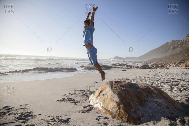 Mixed race boy jumping off rock on beach