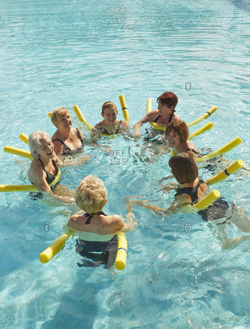 Older Caucasian women playing with foam noodles in swimming pool