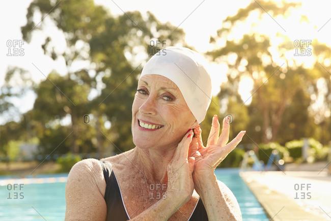 Older Caucasian woman wearing swimming cap in pool