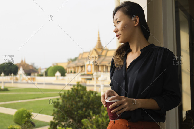 Asian businesswoman admiring view from cafe window, Phnom Penh, Cambodia