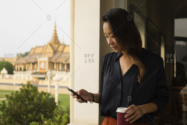 Asian businesswoman using cell phone at window, Phnom Penh, Cambodia