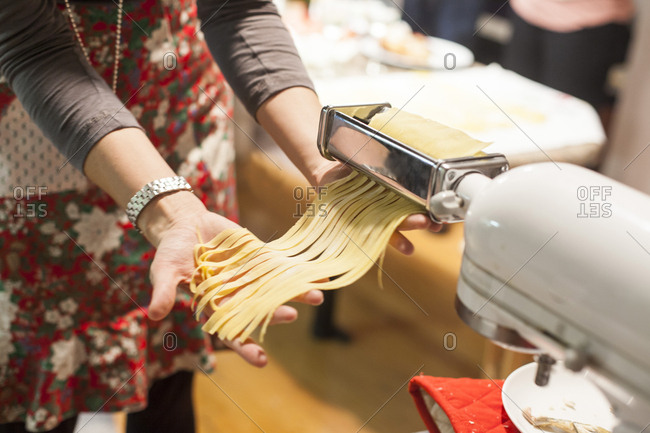 Woman rolling sheets of pasta in kitchen