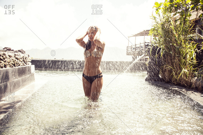 Woman splashing in pool outdoors