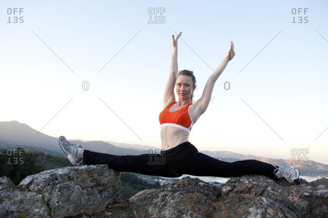 Caucasian woman practicing yoga on mountaintop