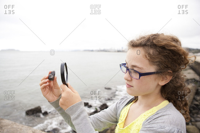 Caucasian girl examining stone with magnifying glass