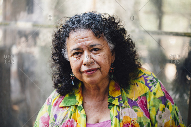 Hispanic woman smiling in smoky backyard