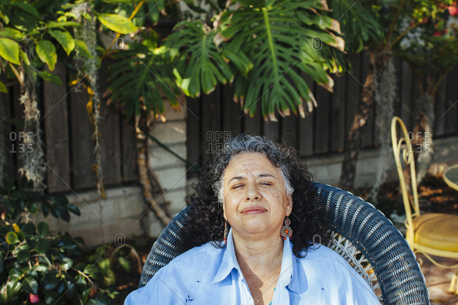 Hispanic woman relaxing in backyard