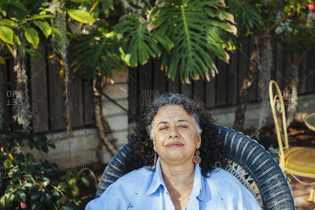 Hispanic woman relaxing in backyard