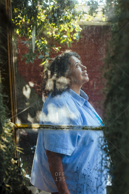 Hispanic woman behind window looking up in backyard