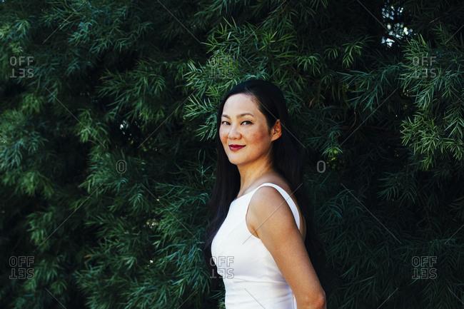 Korean bride smiling under trees