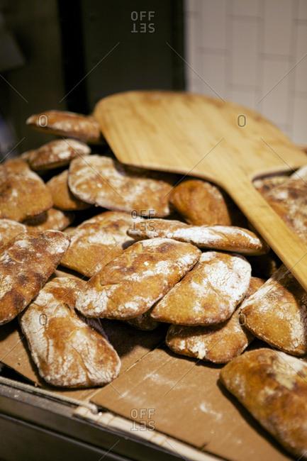 Bread peel on pile of homemade loaves