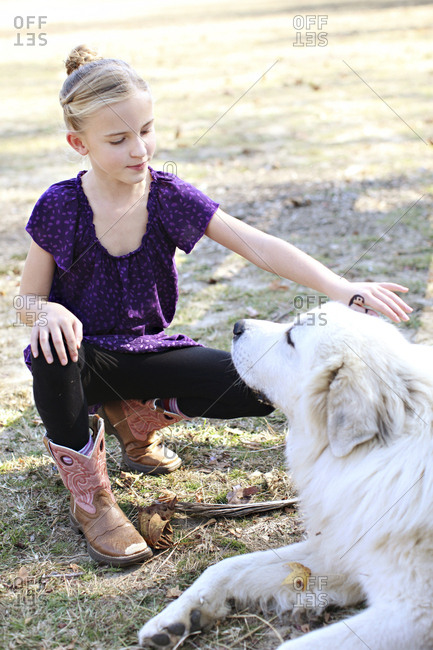 Caucasian girl petting dog in field