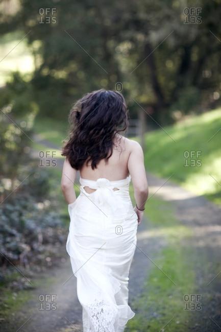 Rear view of bride walking on rural dirt road