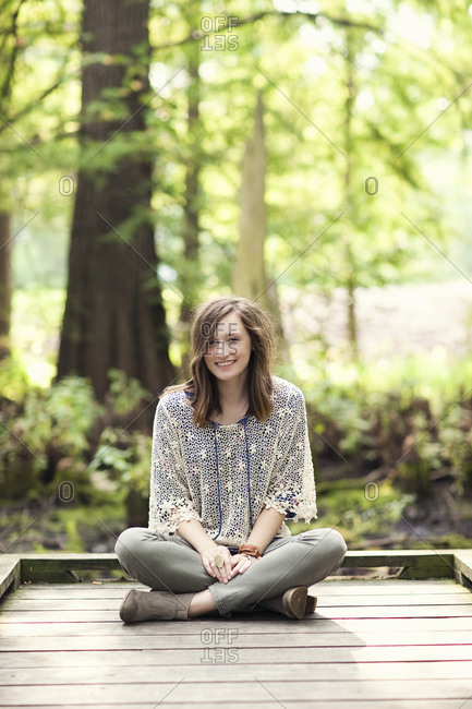 Girl sitting on wooden patio near tree