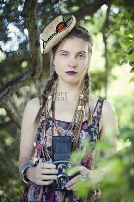 Stylish woman photographing with vintage camera