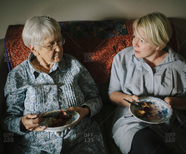 Older woman and granddaughter eating on sofa