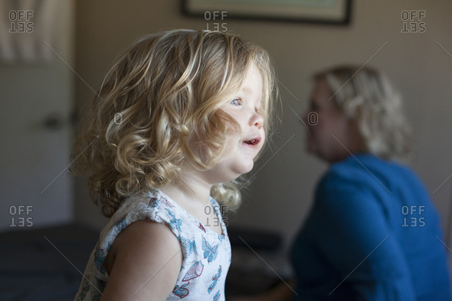 Close up of curious preschooler girl near grandmother