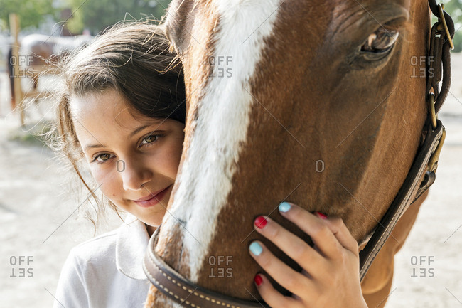 Close up of teenage girl hugging horse