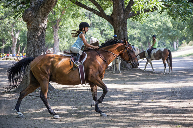 Equestrian girl riding horse on ranch