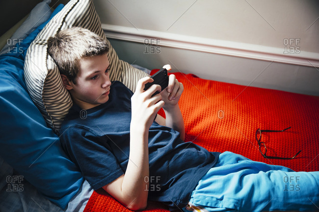 Caucasian boy using cell phone on bed