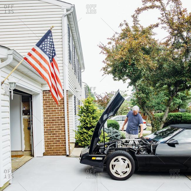 Caucasian man repairing car in driveway