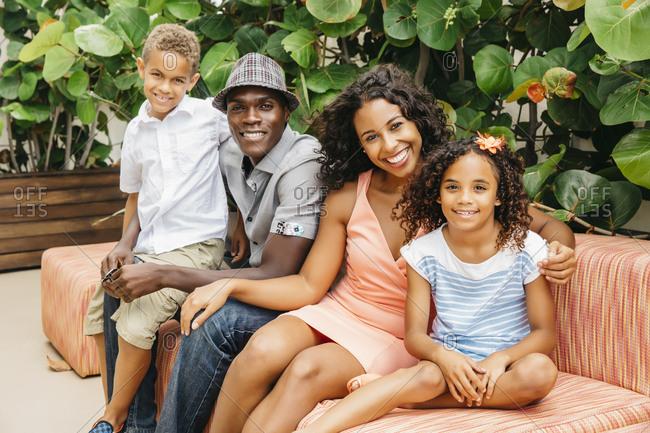 Family smiling on sofa in garden
