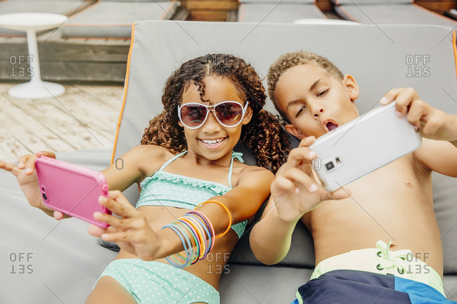 Mixed race children taking selfie with cell phones on patio