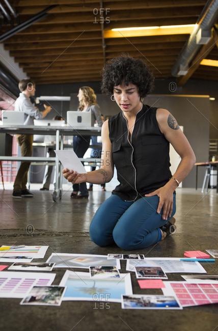 Businesswoman examining paperwork on office floor
