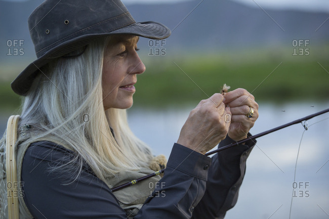 Caucasian woman tying fishing line in remote lake