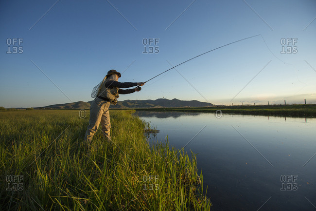 Caucasian woman casting fishing line in remote lake