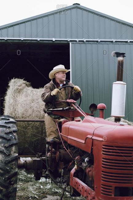 Caucasian farmer driving tractor on farm