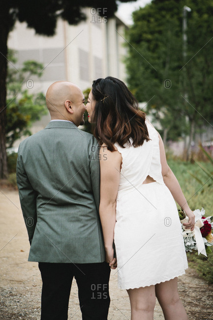 Japanese newlywed couple kissing outdoors