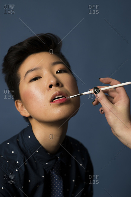 Androgynous woman having makeup applied