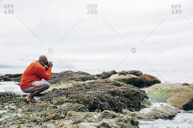Black man photographing on beach